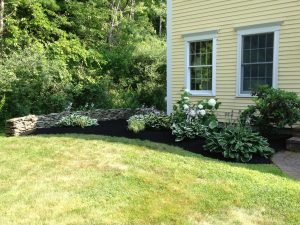 Photo of well mulched garden next to a stone wall with a mowed lawn in front