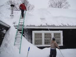 photo of men removing snow from the roof